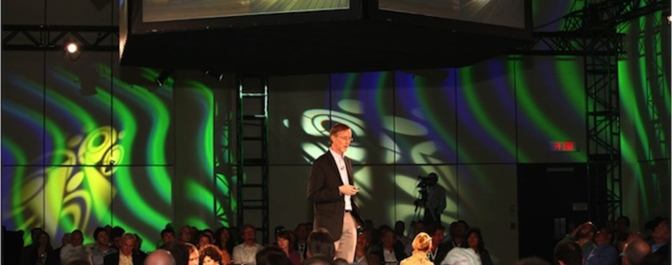 "A Greenbuild 2012 speaker in a ""special set"" room, featuring a unique stage and"